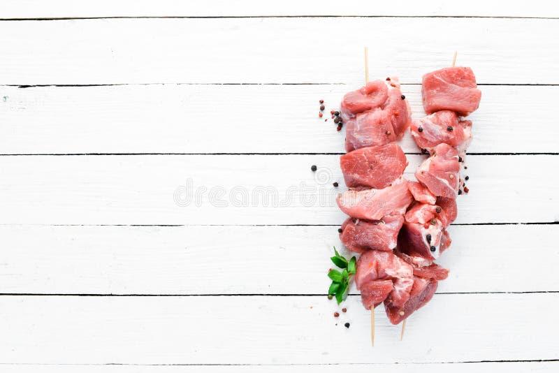 Kebab sin procesar del shish carne de la barbacoa con las especias y las hierbas En un fondo de madera blanco foto de archivo libre de regalías