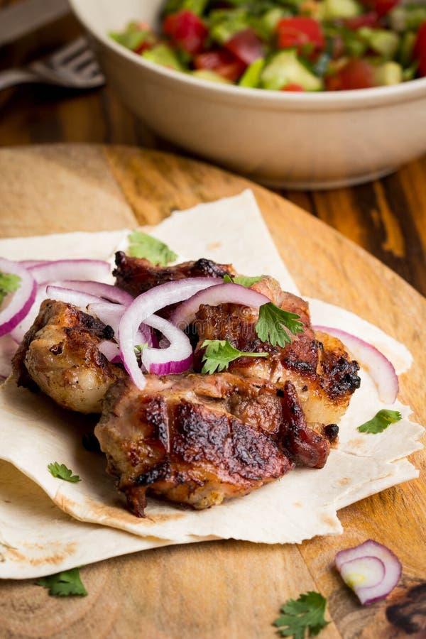 Kebab stycken av kött, nötkött, griskött på tunn pitabröd med löken, sallad arkivbilder