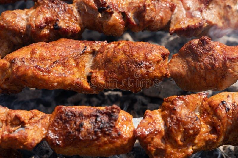 Kebab succoso saporito arrostito della carne di maiale che cucina sugli spiedi del metallo sulla griglia del carbone con il fumo  fotografie stock