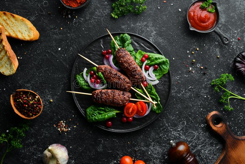 Kebab. Traditional middle eastern, arabic or mediterranean meat kebab with vegetables and herbs. Top view. Free space for your text royalty free stock images