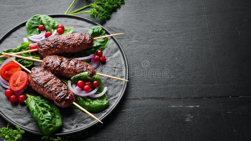 Kebab. Traditional middle eastern, arabic or mediterranean meat kebab with vegetables and herbs. Top view. Free space for your text stock image
