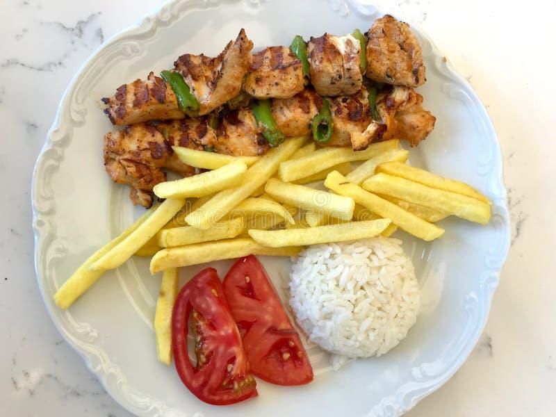 Kebab turco del pollo con riso Pilav o patate e pomodoro/Sis Kebap del pilaf immagine stock