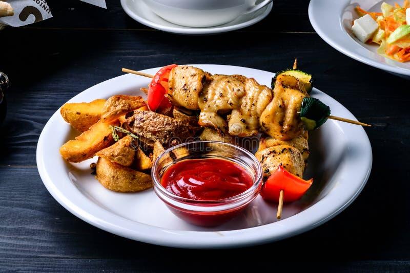 Kebab y salsa en una tabla negra en un restaurante del café imagenes de archivo