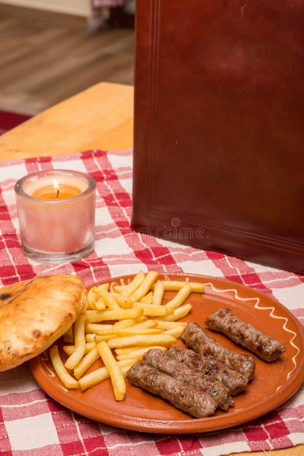 Kebaber tjänade som med franska småfiskar för potatisen med menyboken royaltyfria foton