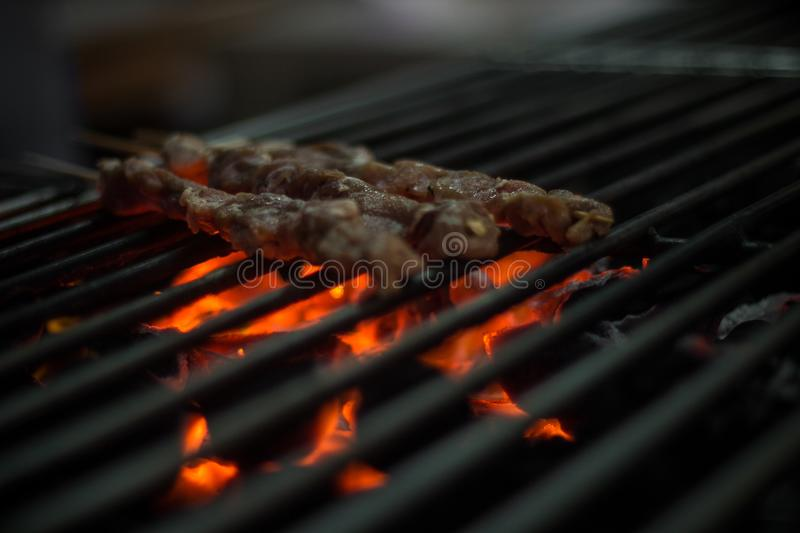 Kebabs of meat sizzling on grill stock photos