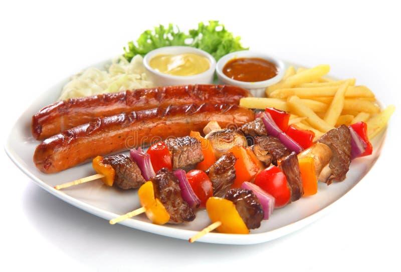 Kebabs y salchicha gastrónomos con las fritadas en la placa fotos de archivo libres de regalías