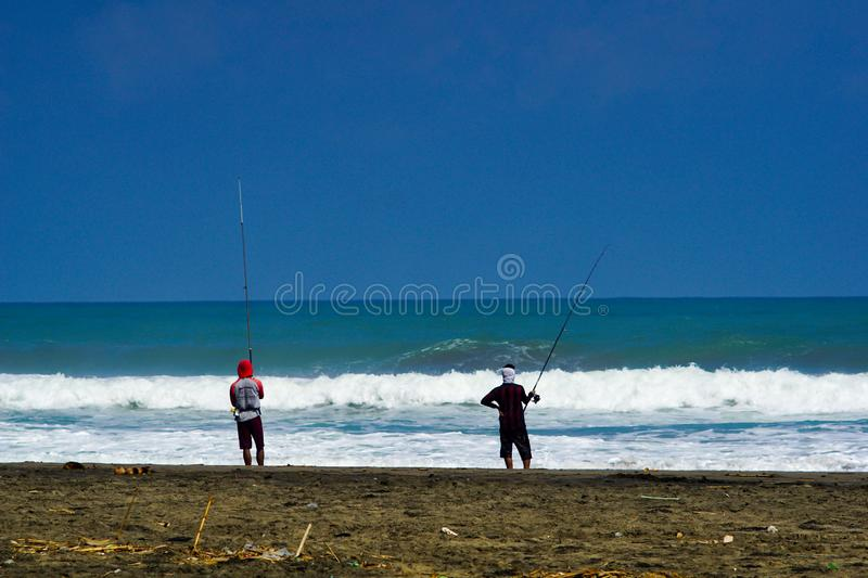 Kebumen, Central Java, Indonesia- June 17, 2018 : Fisherman are fishing by the beach with great waves. Person, sea, water, coast, job, storm, ocean, nature stock photography