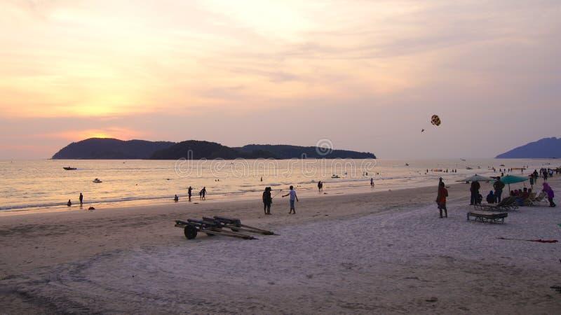 KEDAH, LANGKAWI, MALÁSIA - 8 de abril de 2015: Turistas que têm o momento romântico durante o por do sol na praia de Cenang imagens de stock