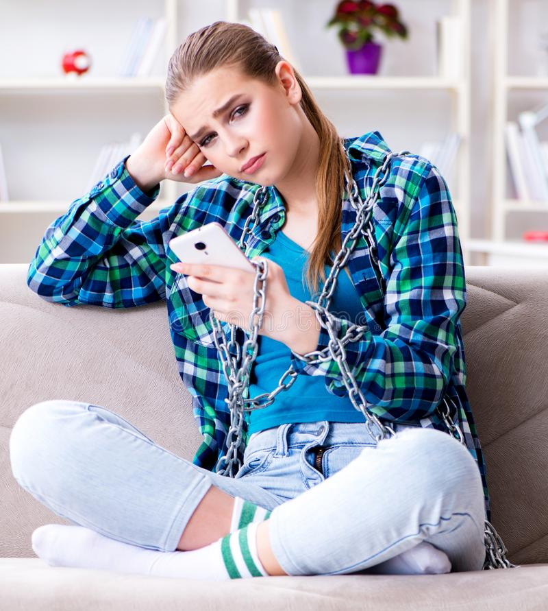 Kedjad fast kvinnlig student med mobilt sammantr?de p? soffan royaltyfri foto