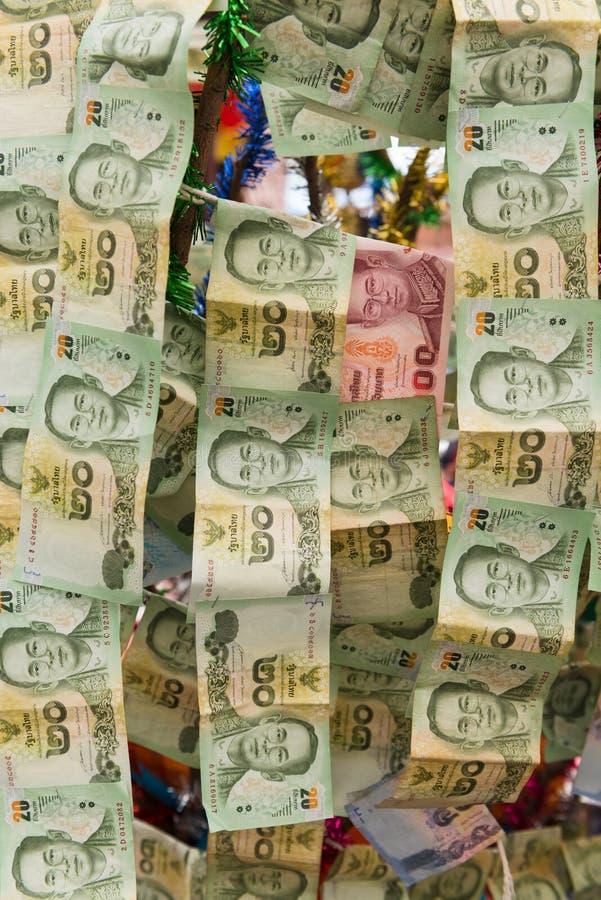 Kedjor av thailändska pappers- pengar hängde att erbjuda för bra lycka arkivfoton