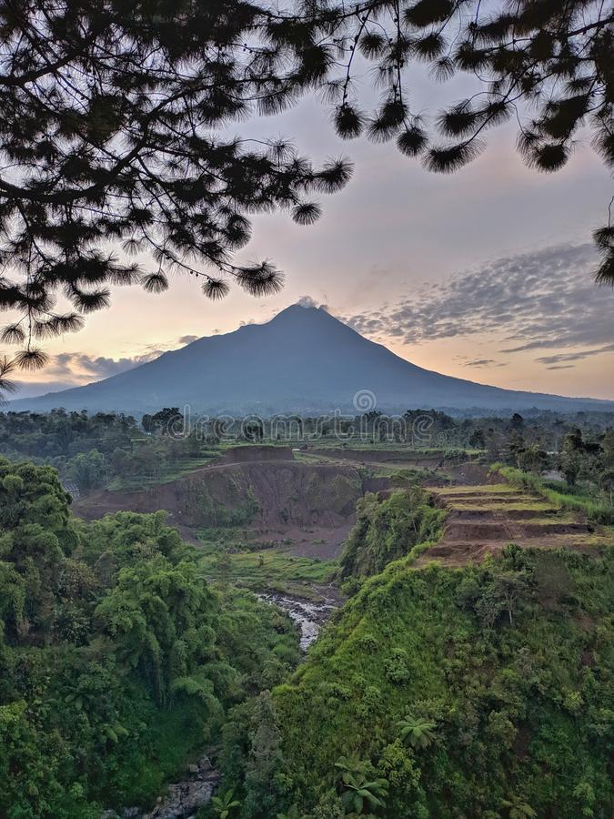 Kedung kayang waterfall and Merapi mountain view. Sunrise with forest scenery. Magelang, Indonesia. Beautiful scenery royalty free stock images