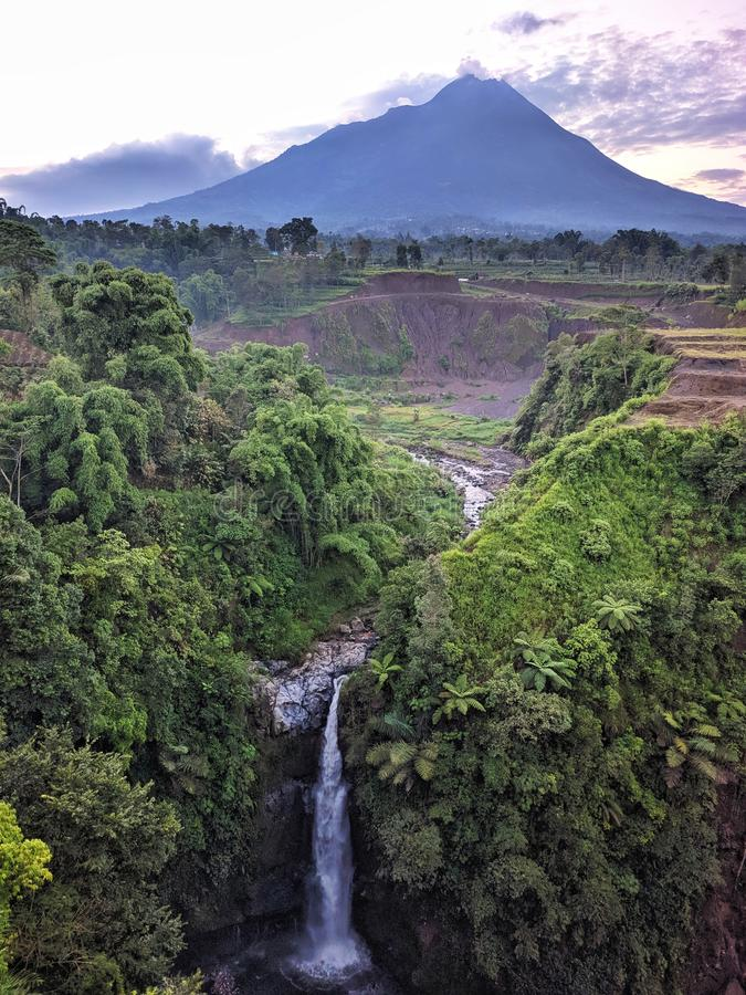 Kedung kayang waterfall and Merapi mountain view. Sunrise with forest scenery. Magelang, Indonesia. Beautiful scenery royalty free stock photography