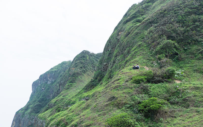 Keelung , Taiwan - March 29, 2017 : A couple of tourist sitting. Keelung, Taiwan - March 29, 2017 : A couple of tourist sitting on top of the mountain stock photography