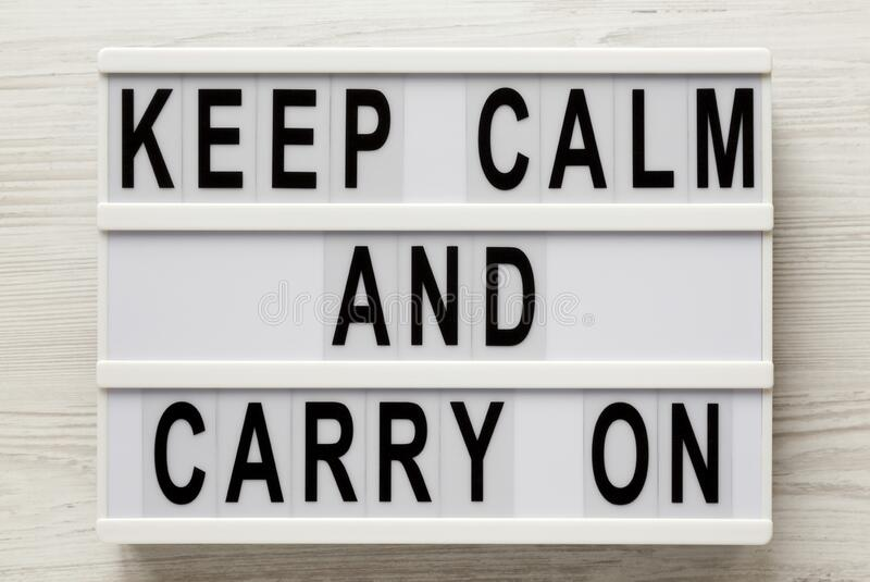 `Keep calm and carry on` words on a lightbox on a white wooden background, top view. Overhead, from above, flat lay.  royalty free stock photo