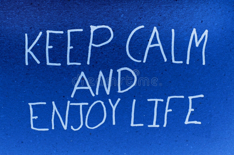 Keep calm and enjoy life. Wrote on blue background stock photo