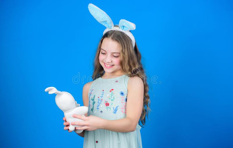 Keep calm and happy Easter. Little girl and rabbit toy. Small girl in rabbit ears with Easter toy. Little child in stock photo