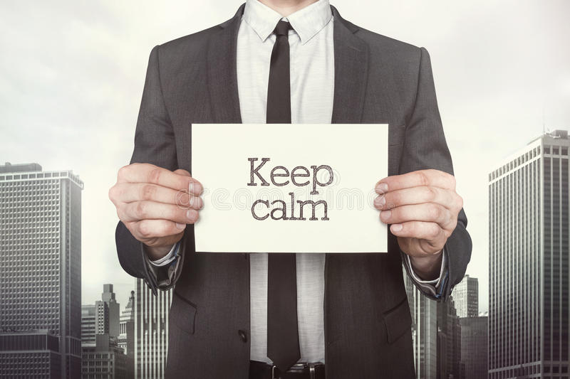 Keep calm on paper. What businessman is holding on cityscape background royalty free stock photos