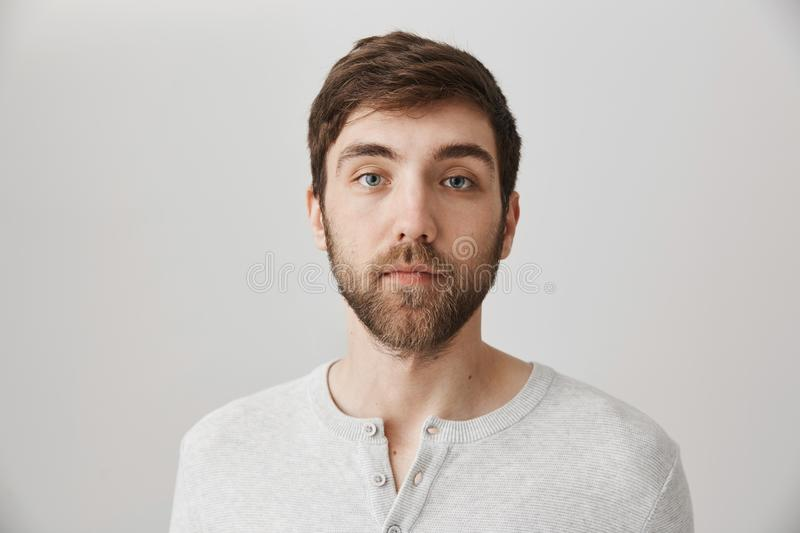 Keep calm and pretend nothing happened. Portrait of calm serious mature male with beard standing with no emotions over stock photo