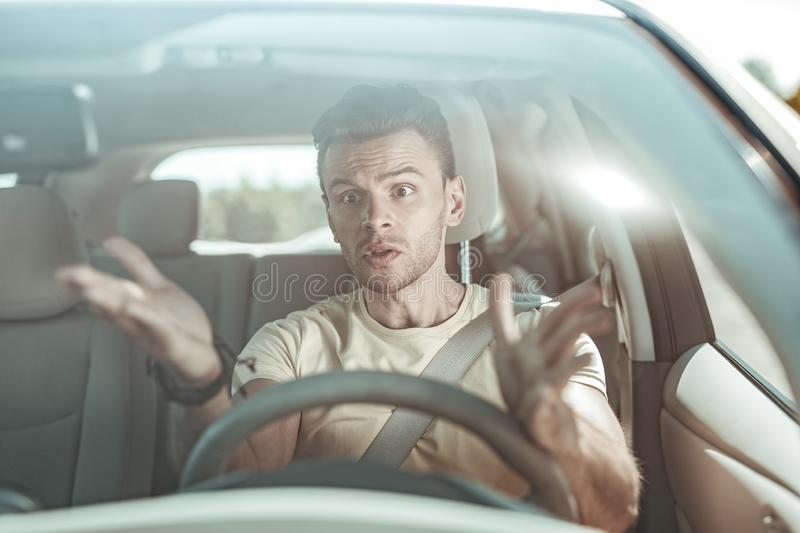 Emotional young male person wrinkling his forehead. Keep calm. Serious man actively gesticulating while driving his car stock photo