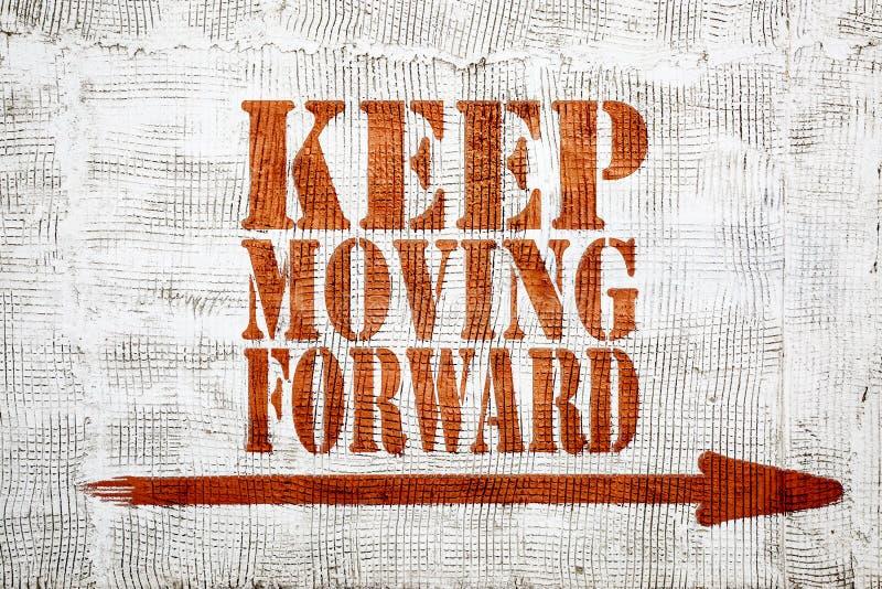 Keep che muove in avanti - i graffiti sulla parete dello stucco immagini stock libere da diritti