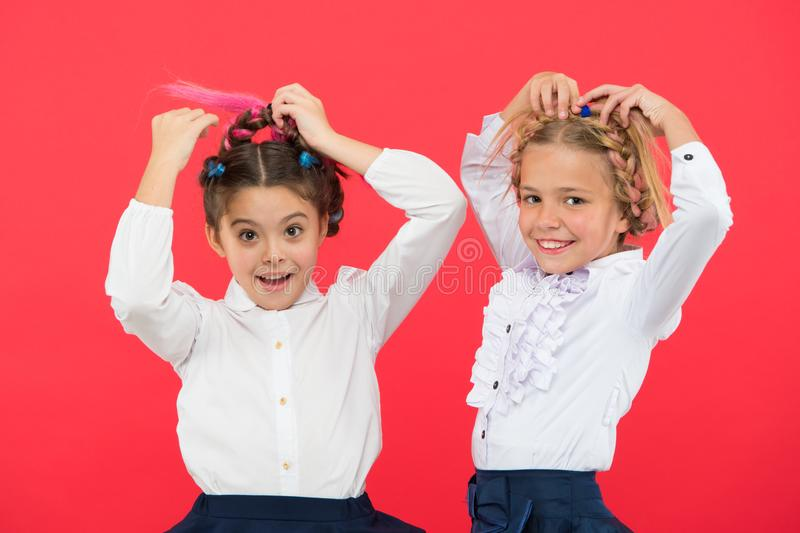 Keep hair braided for tidy look. Kids pupils play with long braided hair. Hairdresser salon. Hairstyles which suits to stock image