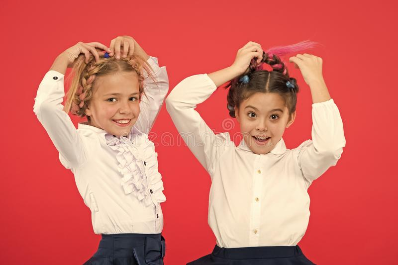 Keep hair braided for tidy look. Kids pupils play with long braided hair. Hairdresser salon. Hairstyles which suits to. Formal school style. Appropriate royalty free stock photo