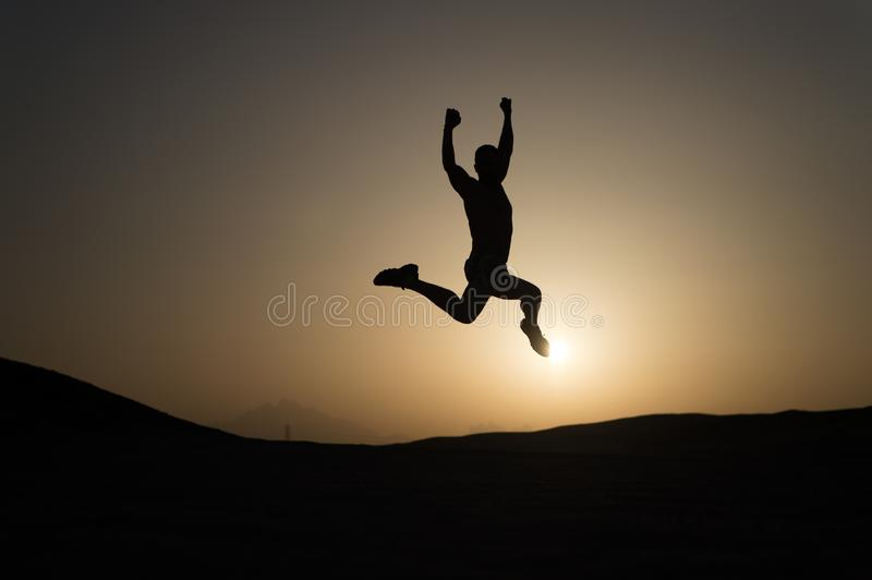 Keep moving. Silhouette man motion jump in front of sunset sky background. Daily motivation. Healthy lifestyle personal royalty free stock photo