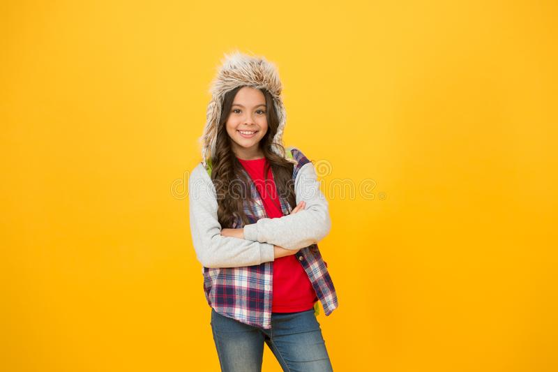 Keep out cold in winter. Small girl smile in faux fur hat yellow background. Happy child wear fashion winter accessory stock photography