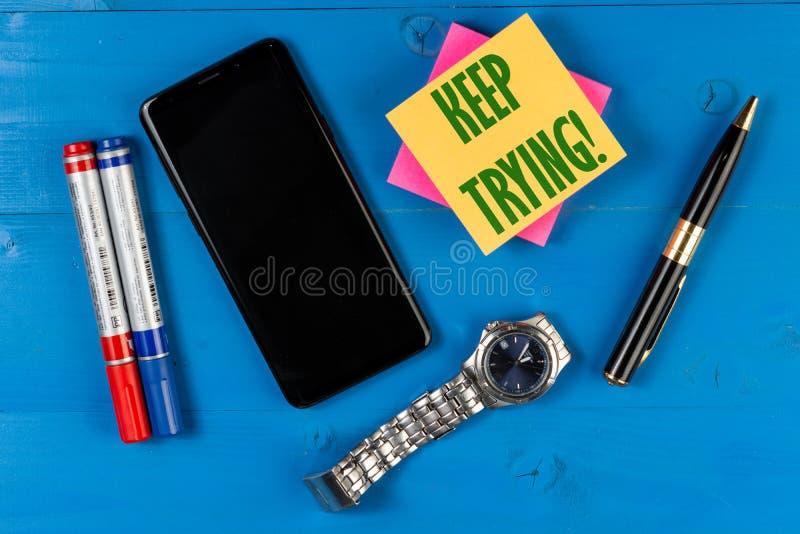 Keep que intenta en el papel del bloque Pantalla negra vacía en el teléfono móvil con el espacio de la copia imagenes de archivo