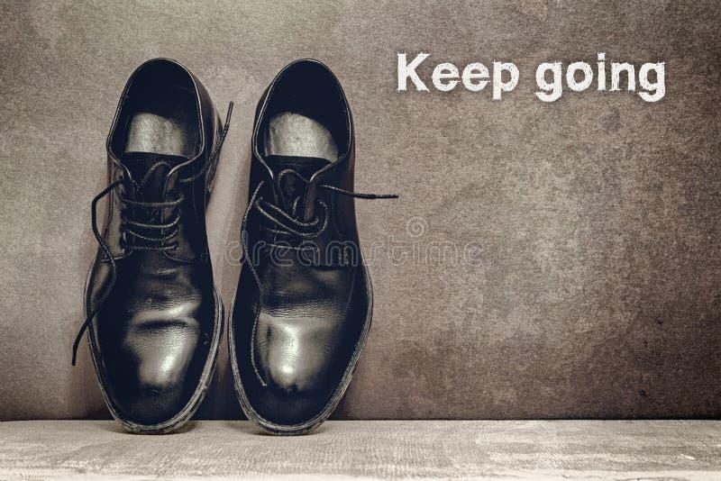 Keep que vai em sapatas marrons da placa e de trabalho no assoalho de madeira fotos de stock royalty free