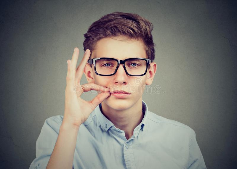 Keep a secret, young man zipping his mouth shut. Quiet concept royalty free stock photos