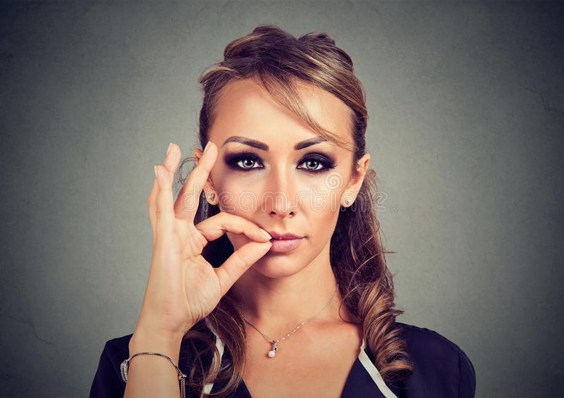 Keep a secret, young woman zipping her mouth shut. Quiet concept royalty free stock photography