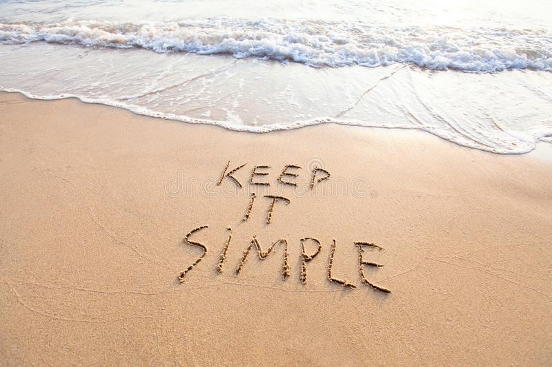 Keep it simple. Words written on sand, simplicity concept royalty free stock photography