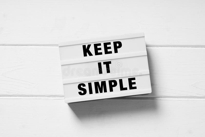 Keep it simple text on lightbox sign. Minimal flat lay design on white wooden background, simplicity or minimalism concept stock photography