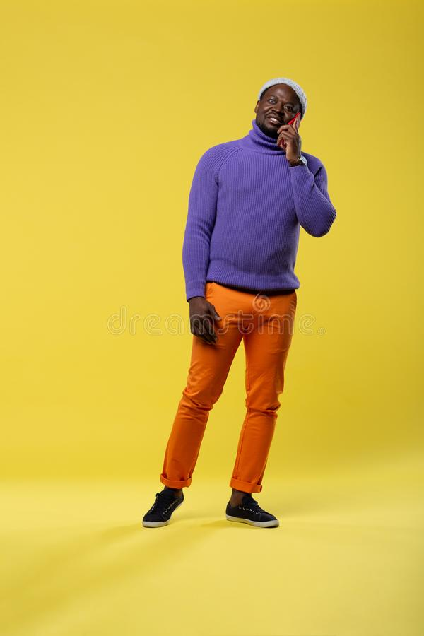 Cheerful brunette man demonstrating colorful stylish clothes. Keep smiling. Pleased young male expressing positivity while communicating per telephone royalty free stock images
