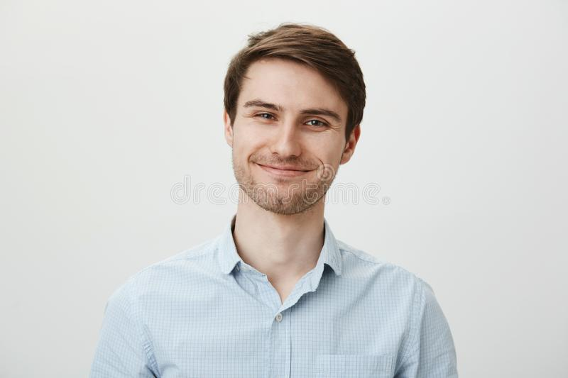 Keep talking but I do not care. Portrait of polite bothered attractive office worker in casual shirt pulling fake smile. And trying to look friendly while stock images