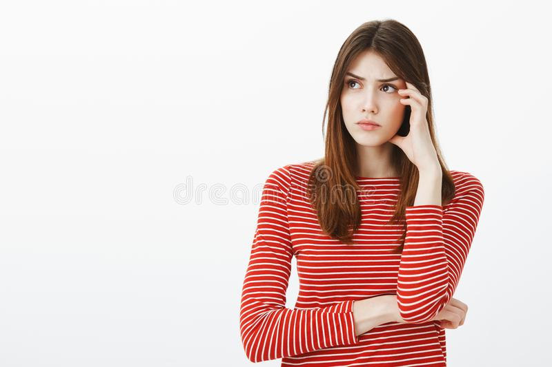 Keep thinking and ideas will come. Portrait of focused attractive smart woman in striped clothes, looking aside and stock photo