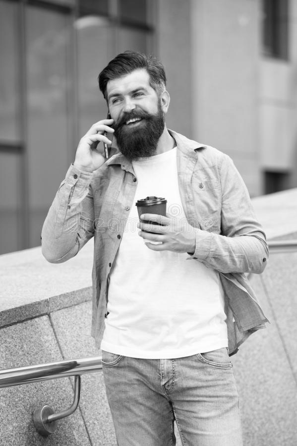 Keep in touch. Man bearded walk with smartphone and coffee cup urban background. Man smiling face smartphone. Guy stock photography