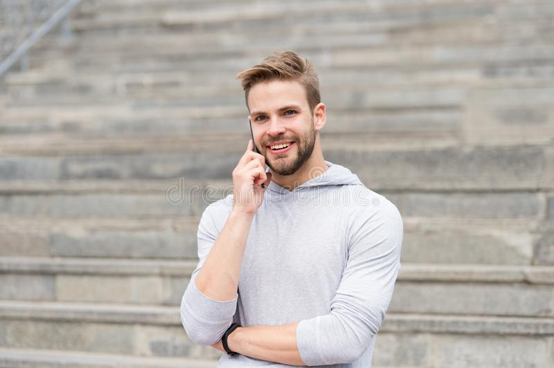 Keep in touch. Man bearded walks with smartphone, urban background with stairs. Man pleasant smiling face speaks on royalty free stock photo