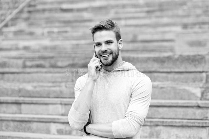 Keep in touch. Man bearded walks with smartphone, urban background with stairs. Man pleasant smiling face speaks on stock photo
