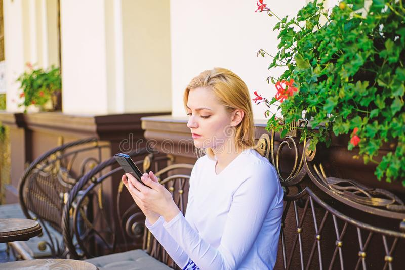 Keep in touch. Woman calm face texting smartphone cafe terrace urban background. Lady texting message friend white spend. Time in cafe. Girl communicating with stock photography