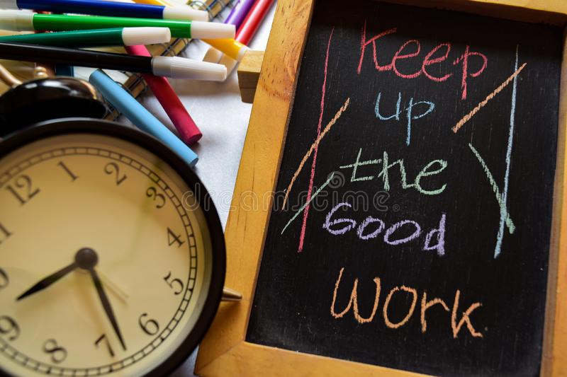 Keep up the good work on phrase colorful handwritten on chalkboard, alarm clock with motivation and education concepts royalty free stock images