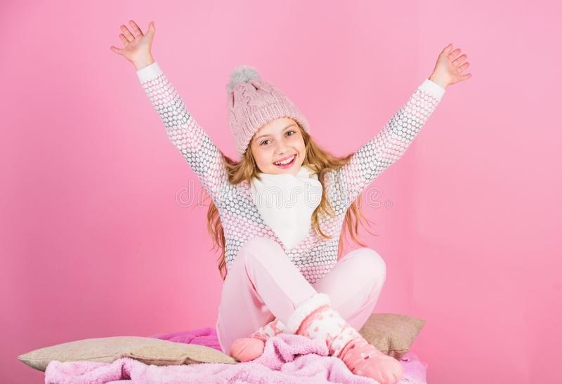 Keep warm and comfortable. Kid girl wear knitted hat relaxing pink background. Child long hair warm woolen hat enjoy stock images
