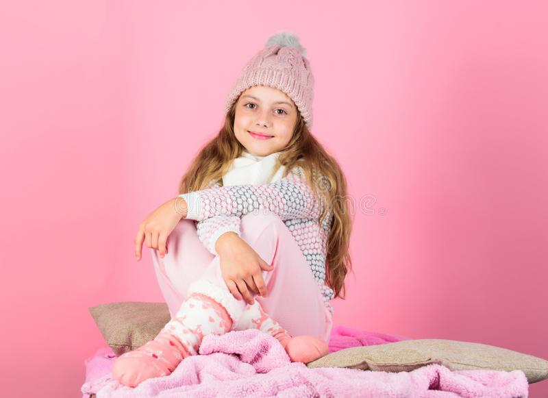 Keep warm and comfortable. Warm accessories that will keep you cozy this winter. Kid girl wear knitted hat relaxing pink. Background stock image