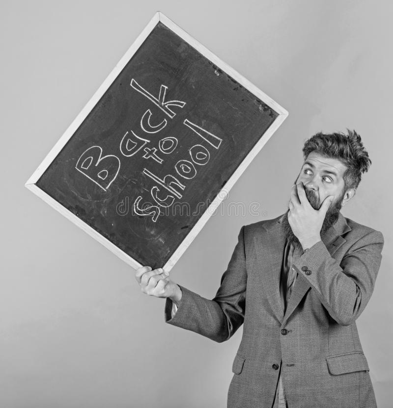 Keep working. Teacher with tousled hair stressful about school year beginning. Teacher bearded man holds blackboard with. Inscription back to school green stock images