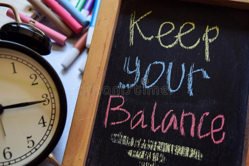 Keep your balance. On phrase colorful handwritten on chalkboard, alarm clock with motivation and education concepts stock photos