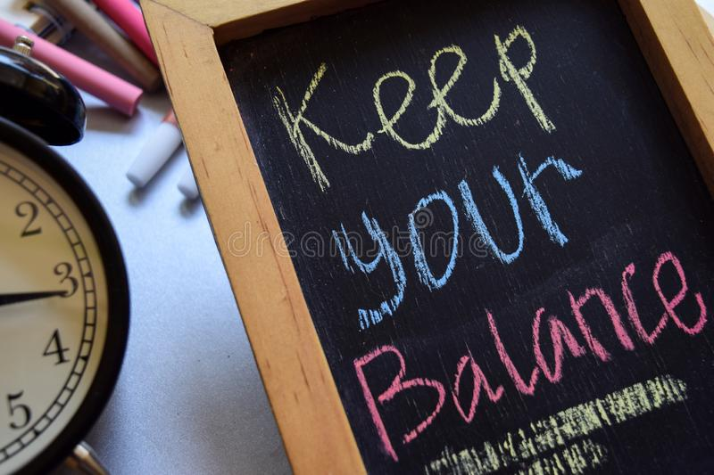 Keep your balance on phrase colorful handwritten on chalkboard royalty free stock photo