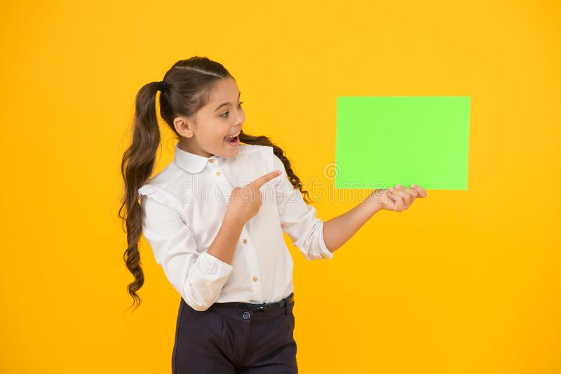 Keep your eye out for the idea. Happy girl pointing finger at certain idea on yellow background. Small cute kid smiling stock photo