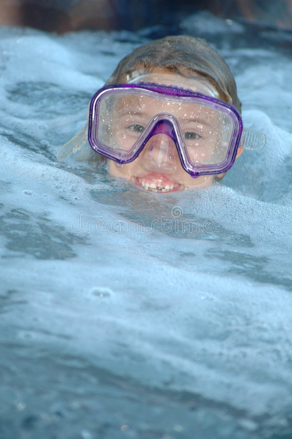 Keep your head above the water. Child playing in water with face mask on stock images