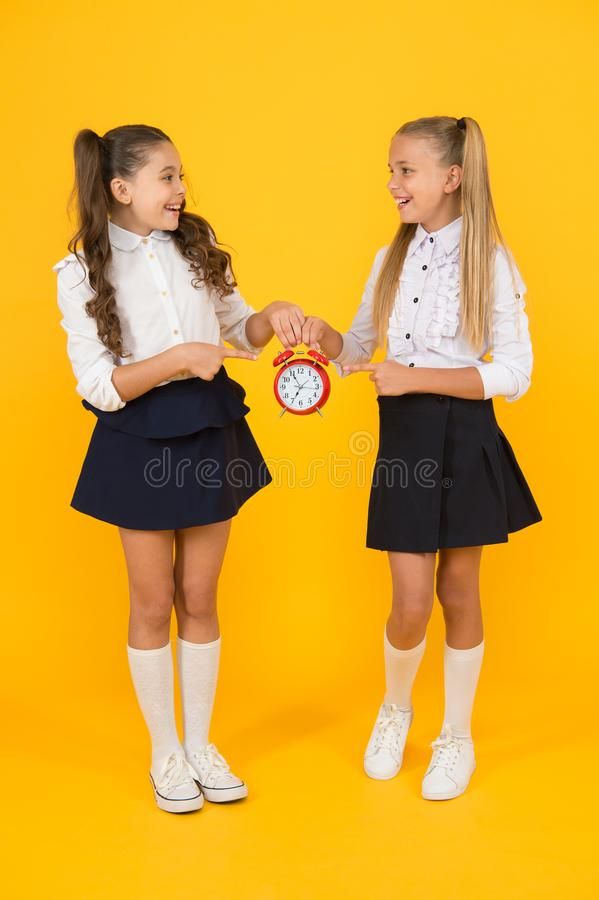 Keep your students safe and on time. Happy little girls holding retro clock during school time on yellow background royalty free stock images
